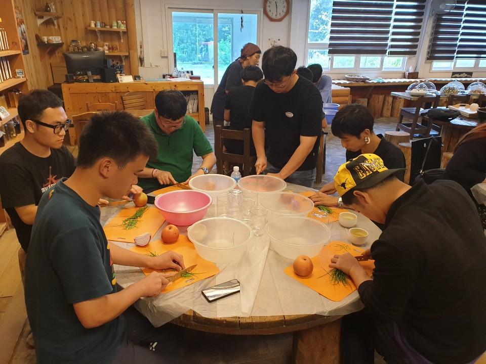 원형 탁상에 둘러 앉아 식재료를 다듬고 있는 사람들의 모습