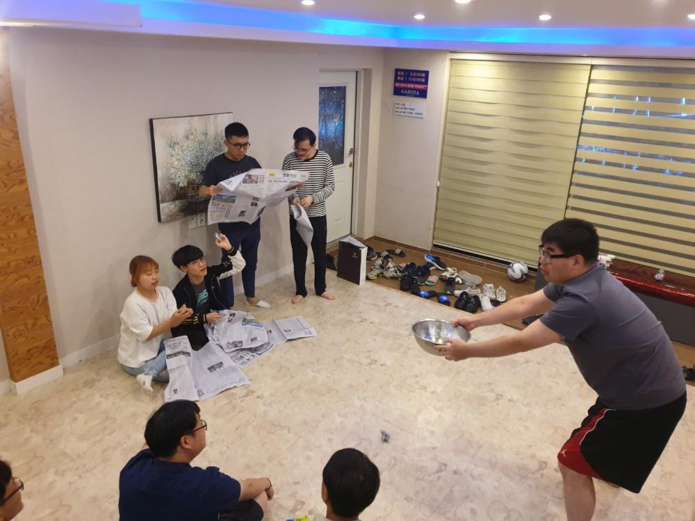 한 참가자가 그릇을 들고 있고, 다른 참여자들은 신문을 말아 그릇속에 던져 넣으려 하고 있는 모습